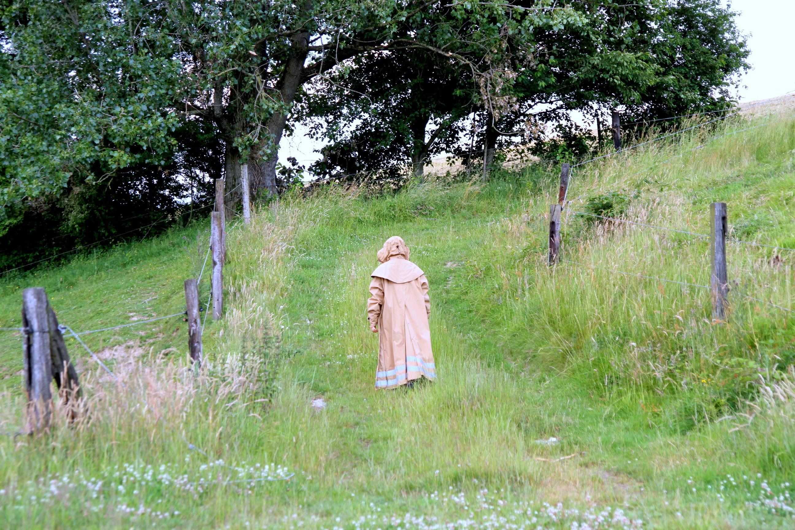 Frua mit bodenlangem Regenmantel auf dem Weg zur Koppel